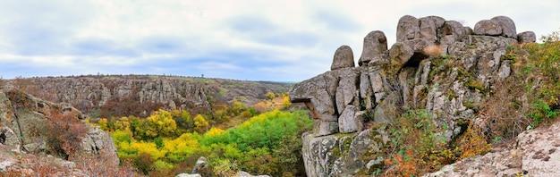 Осенние деревья и большие каменные валуны вокруг