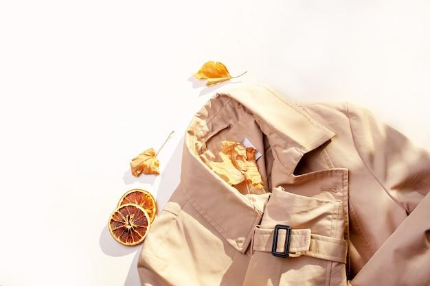가 트렌치 코트와 흰색 바탕에 단풍. 플랫 레이 스타일