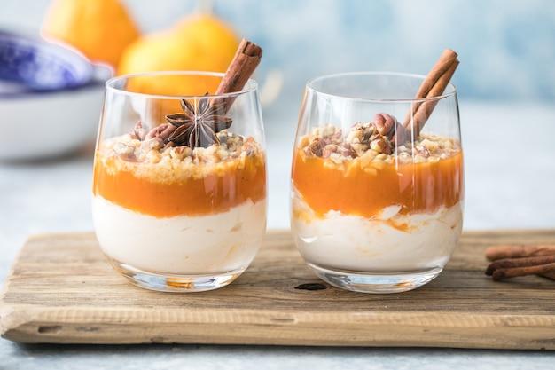 Осенний мелкий десерт. слоистое тыквенное парфе, десерт из орехов пекан в стакане, с осенними украшениями.