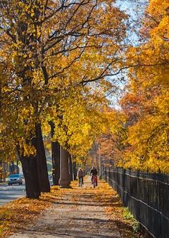 Осенний городской солнечный пейзаж с велосипедистами.