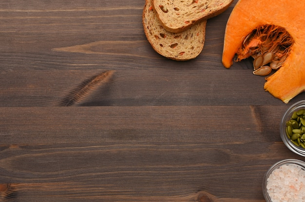 Autumn vegetable wooden background with slice of ripe pumpkin, carrot organic bread, seeds and pink hawaii salt border.