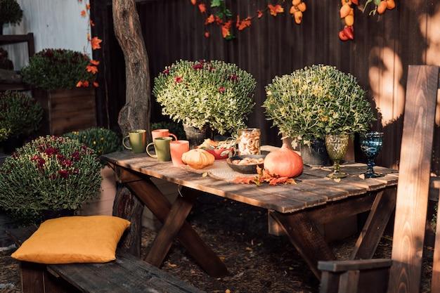 Осенние овощи и цветы красиво выложены на столе во дворе