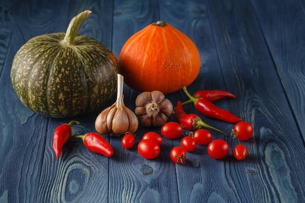 秋の野菜料理の準備。青い素朴な背景にカボチャ、トマトの成分