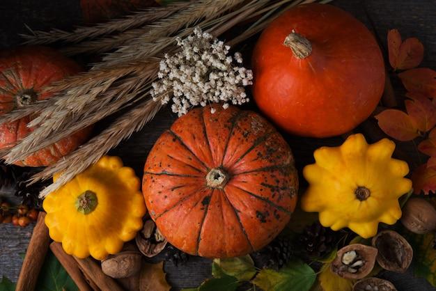 Осенние овощи, опавшие листья, орехи и тыквы на деревянном столе, вид сверху