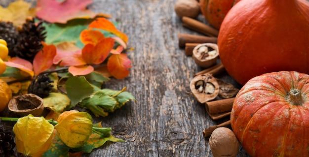 Осенние овощи, опавшие листья, орехи и тыквы на деревянном столе