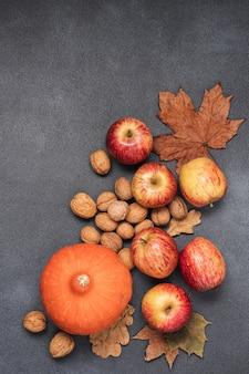 黒の背景に秋の野菜フルーツナッツと乾燥した葉