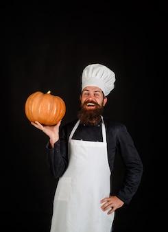 Autumn vegetables healthy vegetarian eating chef preparing meal in kitchen big pumpkin for halloween