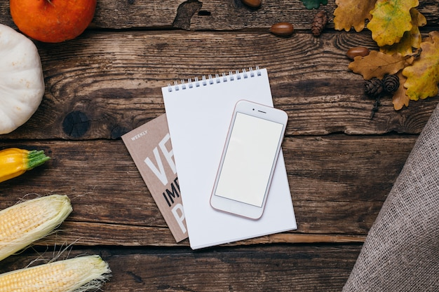 Autumn vegetables: mobile phone with white empty screen, pumpkins and corn with yellow leaves on wood
