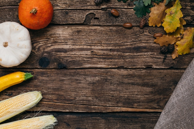 Autumn vegetables: pumpkins and corn with yellow leaves on wood