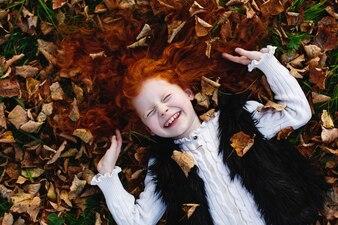秋の雰囲気、子供の肖像画。魅力的で赤い髪の少女は落ちた葉の上に横たわって幸せそうに見えます