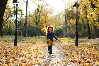 秋の雰囲気、子供の肖像画。魅力的で赤い髪の少女は、歩いているとtで遊んで幸せそうです