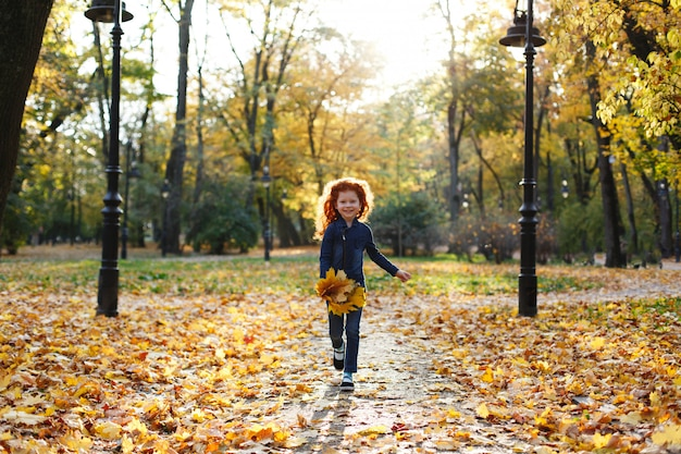 Autumn vibes, child portrait. charming and red hair little girl looks happy walking and playing on t