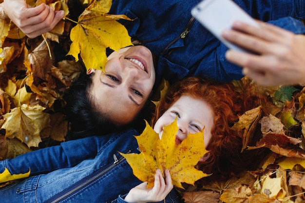 Осенние флюиды, семейный портрет. очаровательная мама и ее рыжая дочь развлекаются, принимая селфи на см