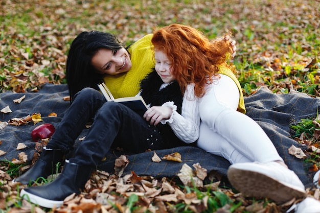 Vibrazioni autunnali, ritratto di famiglia. affascinante mamma e la sua figlia di capelli rossi si divertono seduti sui caduti