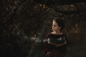 Autumn vibes. Gothic style. Brunette woman in dark red cloth