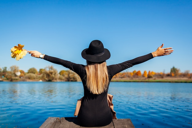 Autumn vibes. young woman relaxing by river with arms raised sitting on pier.
