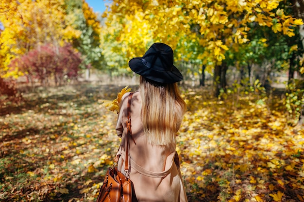 Autumn vibes. young woman walking in autumn forest among falling leaves. stylish girl wearing hat
