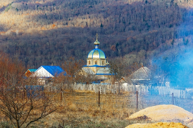 Autumn village landscape with an orthodox church on a forest