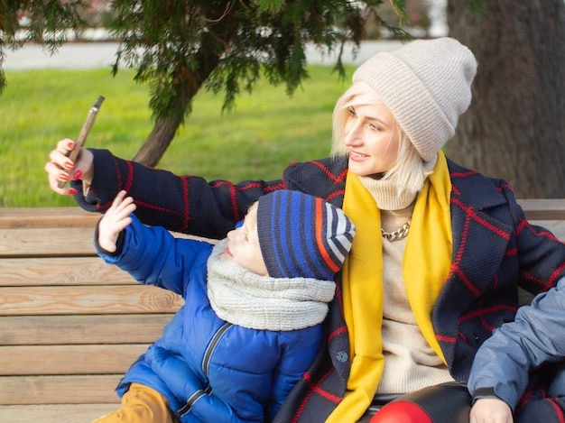 Autumn walk. mom and son are talking on video communication