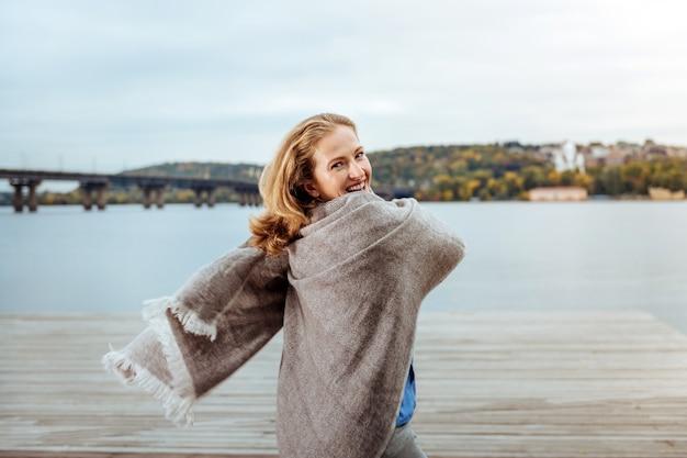 秋の散歩。水の近くを歩いて暖かい格子縞に包まれた笑顔の女性