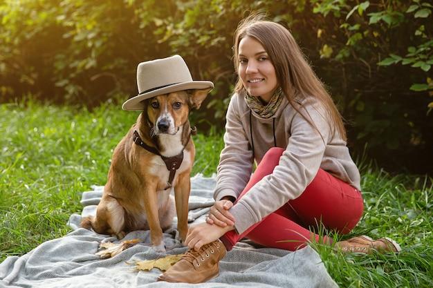 Осенняя прогулка с питомцем. женщина с собакой в шляпе сидит на пледе.