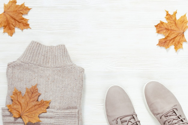 Autumn warm clothes. trendy gray woolen sweater and comfort shoes on white wooden background with copy space.
