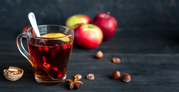 黒い木製にベリーとリンゴの秋の温かいお茶