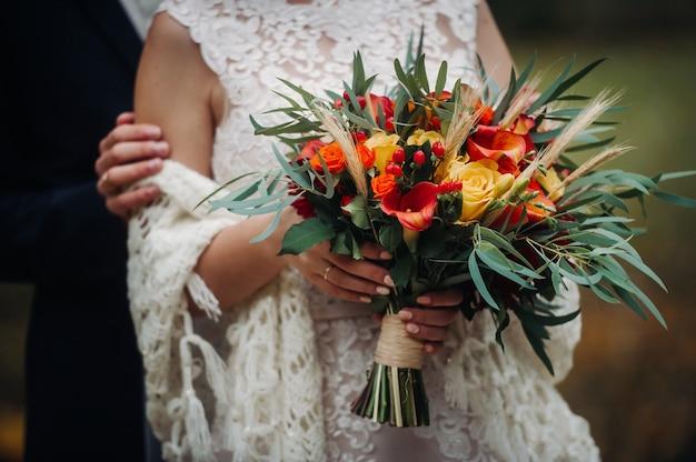 Осенний свадебный букет в руках невесты. прогулка на природе.