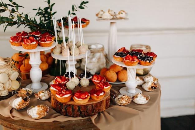 秋の結婚式の甘いバー。ケーキ、カップケーキ、甘さと花。