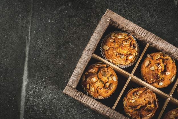 Autumn and winter baked pastries. healthy pumpkin muffins with traditional fall spices, pumpkin seeds. in old wooden box, black stone table,  top view