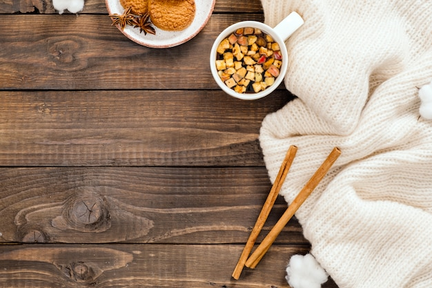 Autumn or winter composition. cup of herbal tea, women fashion white sweater, cinnamon sticks, cotton on wooden background