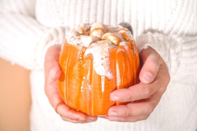 秋、冬の飲み物、クリスマス、感謝祭、ハロウィーンのための飲み物のアイデア。飲み物のスパイシーなカボチャラテ、ホットチョコレート、ホイップクリーム、マシュマロ、カボチャのスパイスと女の子の手