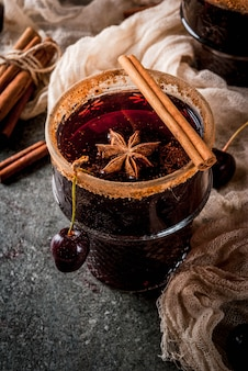 Autumn and winter drinks. hot cherry  sangria with cinnamon, anise, wine and spices. on a stone dark and wooden  with ingredients,
