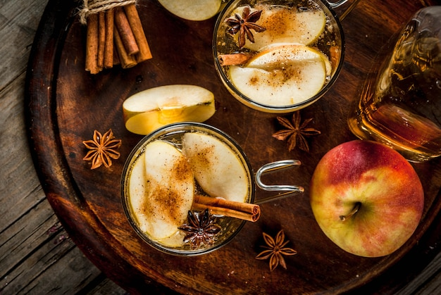 Autumn and winter drinks. traditional home-made apple cider, cocktail of cider with aromatic spices - cinnamon and anise. on an old wooden rustic table, on a tray. copy space top view