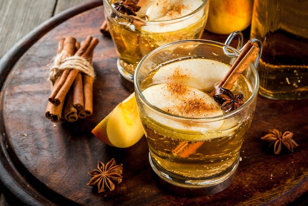 Autumn and winter drinks. traditional home-made apple cider, cocktail of cider with aromatic spices - cinnamon and anise. on an old wooden rustic table, on a tray. copyspace