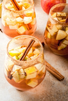 Autumn and winter drinks. warm apple sangria, apple cider with pieces of fruit, cinnamon, spices, sugar. in glasses, on a stone beige table. with the ingredients. copyspace