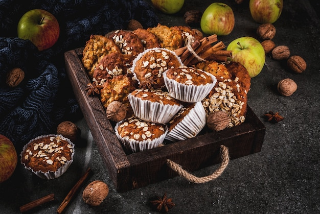 Autumn winter pastries. vegan food. healthy homemade baking cookies, muffins with nuts, apples, oat flakes. cozy home atmosphere, warm blanket, ingredients for baking. dark stone table. copy space