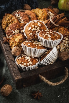 Autumn winter pastries. vegan food. healthy homemade baking cookies, muffins with nuts, apples, oat flakes. cozy home atmosphere, warm blanket, ingredients for baking. dark stone table.