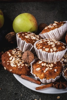 Autumn winter pastries. vegan food. healthy homemade baking cookies, muffins with nuts, apples, oat flakes. cozy home atmosphere, warm blanket, ingredients. dark stone table.