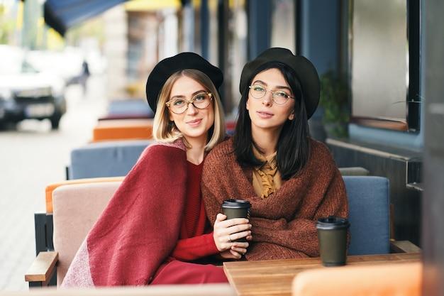 Осенне-зимний портрет двух молодых женщин в летнем кафе, пьет кофе с собой, разговаривает.