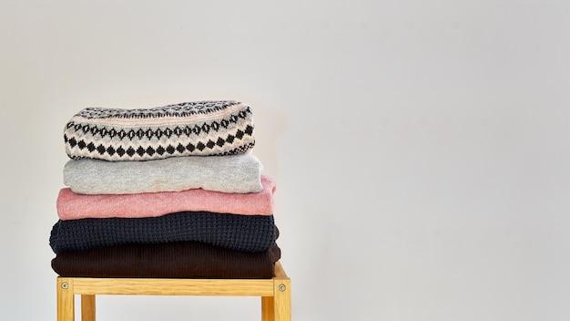 秋冬シーズンのニットウェア。さまざまな編みパターンの暖かいニットセーターのスタック。