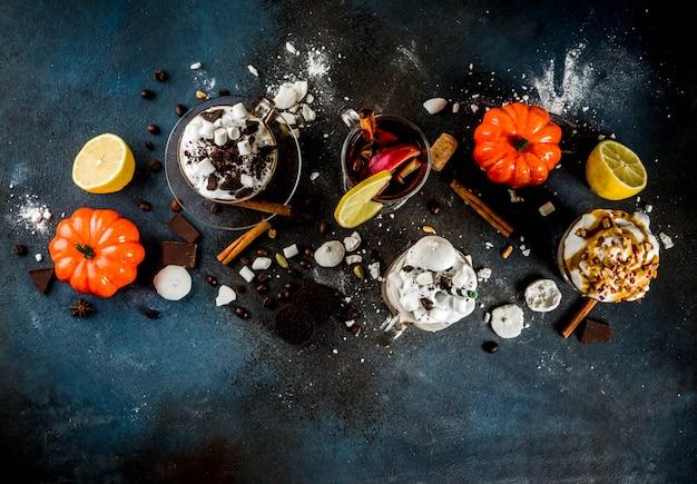 秋冬の暖かい飲み物、ホットチョコレート、カボチャラテ、キャラメルとピーナッツコーヒーラテ、グリューワイン、居心地の良い暗い背景
