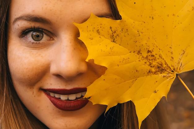 Осенняя женщина держит желтые кленовые листья и прячет глаза