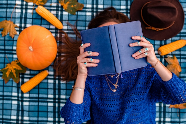 Autumn woman in knitted sweater with book lies on a blue cozy plaid blanket covered with dry maple leaves