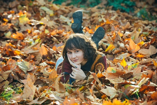 Autumn woman lying over leaves and smiling portrait of a girl girl in autumn orange leaves warm sunn...