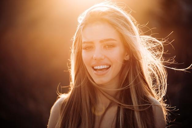 秋の自然の背景に秋の女性。晴れた秋の日に公園で陽気なのんきな女性。秋の旅行と日没。屋外の雰囲気のある瞬間と夢。ライフスタイルのコンセプト。