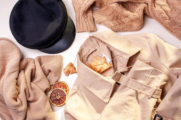 秋の婦人服。白地にトレンチコート、セーター、キャップ。フラットレイスタイル