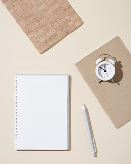 Autumn working  space with open notebook with blank pages and white clock show day time