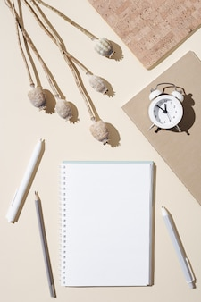 Autumn working  space with open notebook with blank pages and white clock