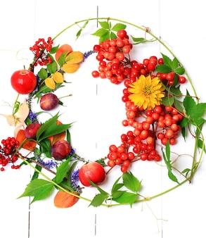 Осенний венок, украшенный ягодами, фруктами, листьями и цветами на белом деревянном фоне, вид сверху